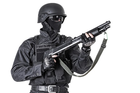 swat: Spec ops police officer SWAT in black uniform with shotgun studio shot