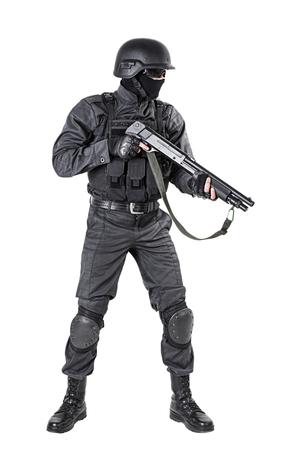 counter terrorism: Spec ops police officer SWAT in black uniform with shotgun studio shot