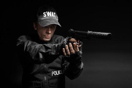 Spec ops police officer SWAT in black uniform with pistol studio 스톡 콘텐츠