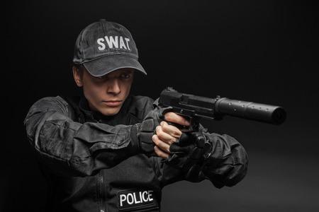 anti nato: Spec ops police officer SWAT in black uniform with pistol studio Stock Photo