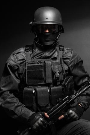 pistol: Spec ops police officer SWAT in black uniform with pistol studio Stock Photo