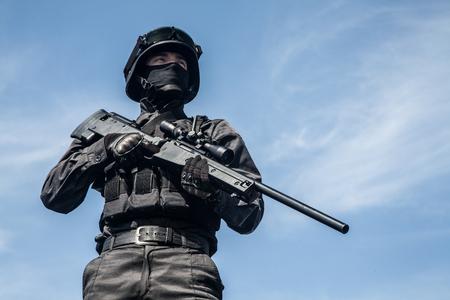anti war: SWAT police sniper in black uniform in action Stock Photo