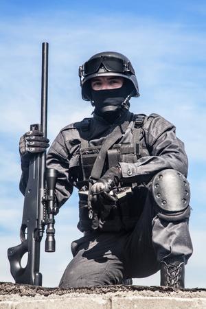 counter terrorism: SWAT police sniper in black uniform in action Stock Photo