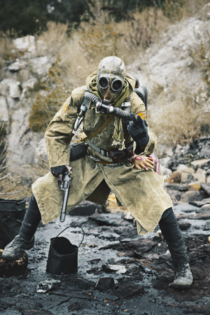 wojenne: Post apocalypse. Sole survivor in tatters and gas mask on the ruins of the destroyed city Zdjęcie Seryjne