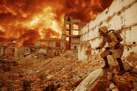 Post apocalypse. Sole survivor in tatters and gas mask on the ruins of the destroyed city Banco de Imagens - 50873366