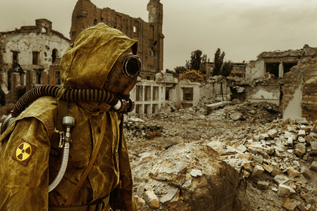 Post apocalypse. Sole survivor in tatters and gas mask on the ruins of the destroyed city Banque d'images