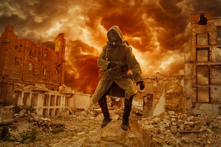 post apocalypse: Post apocalypse. Sole survivor in tatters and gas mask on the ruins of the destroyed city Stock Photo