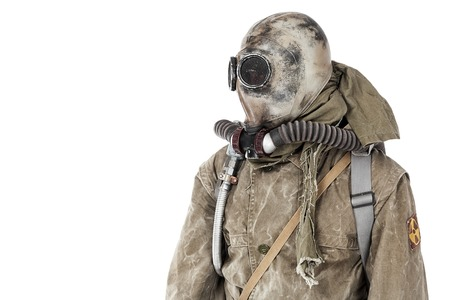 post: Nuclear post apocalypse. Studio shot of survivor in tatters and gas mask Stock Photo