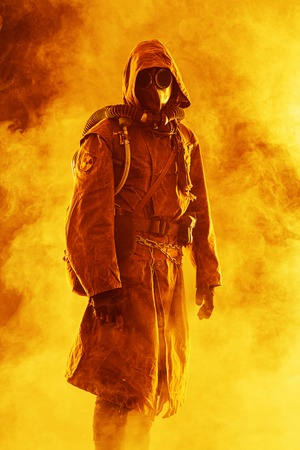 apocalypse: Nuclear post apocalypse. Studio shot of survivor in tatters and gas mask Stock Photo