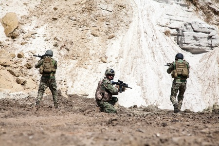 recon: Members of Navy SEAL Team with weapons in action Stock Photo