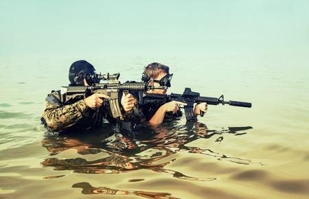 sellos: Hombres rana Navy SEAL con equipo de buceo completo y armas en el agua