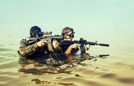 sof: Navy SEAL frogmen with complete diving gear and weapons in the water Stock Photo