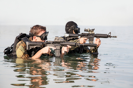 navy seal: Navy SEAL frogmen with complete diving gear and weapons in the water Stock Photo