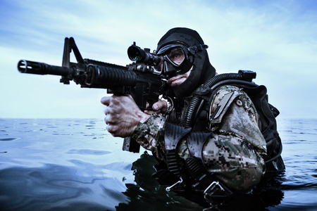 Navy SEAL frogman with complete diving gear and weapons in the water