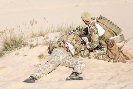 medics: US Army Special Forces soldier medic treating the wounds of injured in the desert