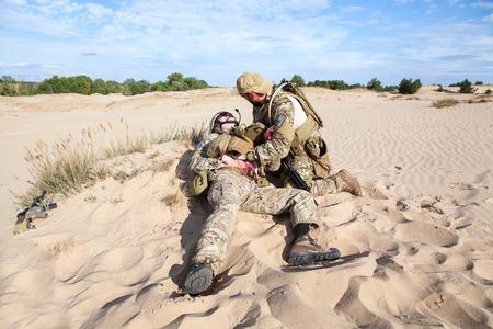soldado: Fuerzas Especiales del Ejército de EE.UU. soldado médico el tratamiento de las heridas de la herida en el desierto Foto de archivo