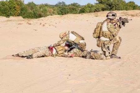 兵士の分隊は煙の中に隠れて腕の中で負傷した仲間を避難させる