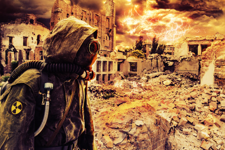 Post apocalypse. Sole survivor in tatters and gas mask on the ruins of the destroyed city Archivio Fotografico