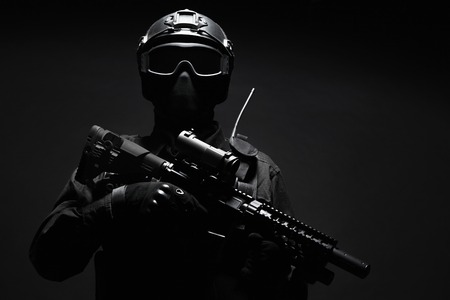face mask: Spec ops police officer SWAT in black uniform and face mask studio shot