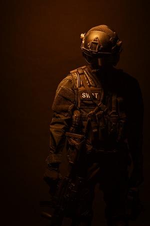 counter terrorism: Spec ops police officer SWAT in black uniform and face mask studio shot