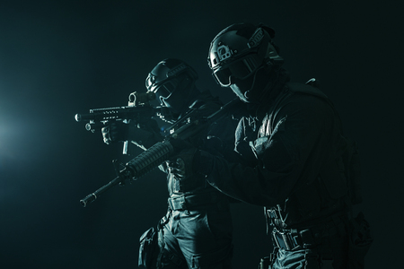 Spec ops police officers SWAT in black uniform and face mask studio shot