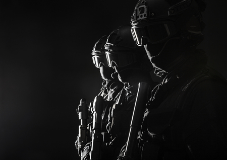 Spec ops police officers SWAT in black uniform and face mask studio shot Фото со стока