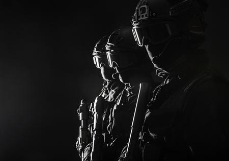 Spec ops police officers SWAT in black uniform and face mask studio shot Zdjęcie Seryjne
