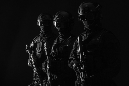 Spec ops police officers SWAT in black uniform and face mask studio shot Archivio Fotografico
