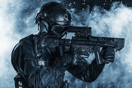 armed: Spec ops police officer SWAT in the rain Stock Photo