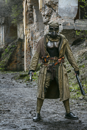survivor: Nuclear post-apocalypse. Sole survivor in tatters and gas mask on the ruins of the destroyed city