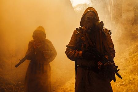 Post-apocalipsis nuclear. Sobrevivientes en los suelos y la máscara de gas sobre las ruinas de la ciudad destruida Foto de archivo - 60823539