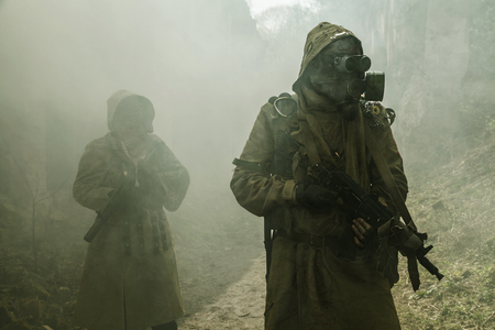 post-apocalypse nucléaire. Survivants en lambeaux et un masque à gaz sur les ruines de la ville détruite