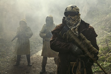 fallout: Nuclear post-apocalypse. Survivors in tatters and gas mask on the ruins of the destroyed city