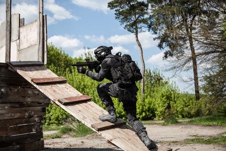 spec: Spec ops police officer SWAT in black uniform in action