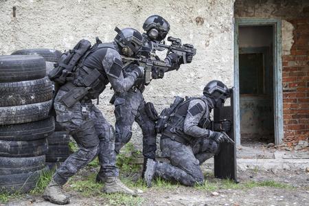 Spec ops police officers SWAT in black uniform in action