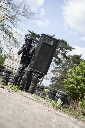 gi: Spec ops police officers SWAT in black uniform in action