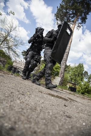 spec: Spec ops police officers SWAT in black uniform in action