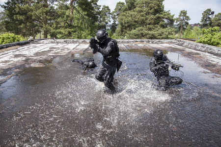 Spec ops police officers SWAT in action in the water Imagens