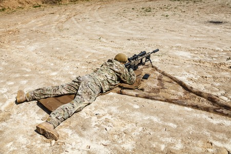 sniper: Young male sniper in camouflage with gun in the desert Stock Photo
