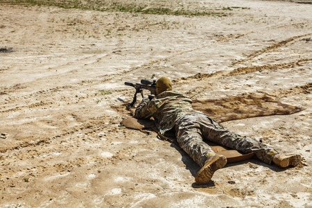 aiming: Young male sniper in camouflage with gun in the desert Stock Photo