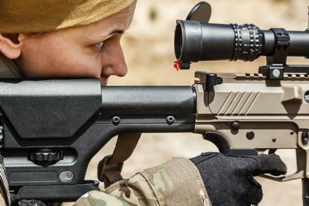 tiro al blanco: francotirador mujer joven en camuflaje con el arma en el desierto
