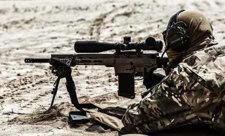 Young male sniper in camouflage with gun in the desert Reklamní fotografie