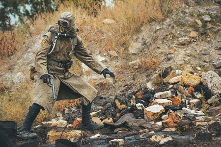 destroyed: Post apocalypse. Sole survivor in tatters and gas mask on the ruins of the destroyed city Stock Photo