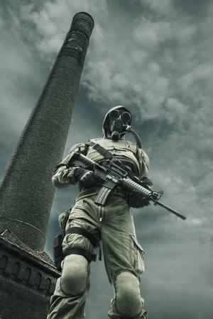 Post apocalypse. Sole survivor in tatters and gas mask on the ruins of the destroyed city Stock Photo