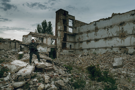 stalker: Post apocalypse. Sole survivor in tatters and gas mask on the ruins of the destroyed city Stock Photo