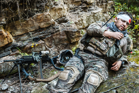 gunner: Wounded army ranger machine gunner in the mountains Stock Photo