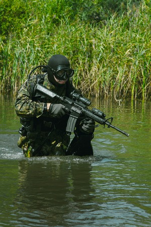 recon: Navy SEAL frogman with complete diving gear and weapons in the water