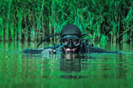 SEAL Navy Froschmann mit kompletter Tauchausrüstung und Waffen im Wasser Standard-Bild - 70000934