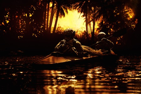 sabotage: Two special forces operators paddling in the military kayak in the jungle at dawn without drawing attention. Diversionary operation ahead