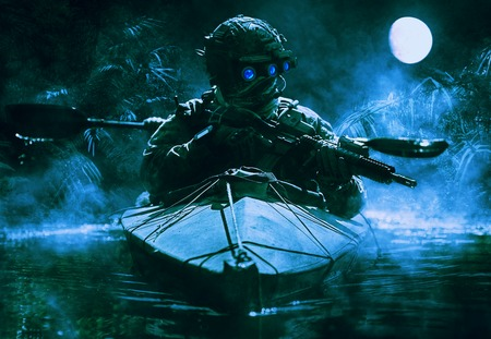 two visions: Two special forces operators with night vision goggles paddling in the army kayak in the jungle. Cloudy night, full moon, damp Stock Photo